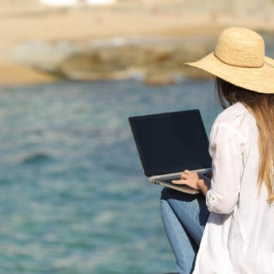 Woman typing on her laptop on the beach